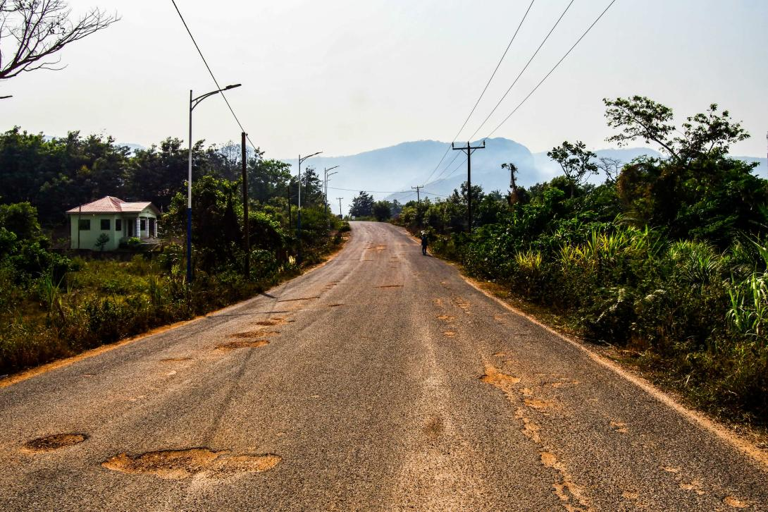 Uneven road in Wli Ghana with a mountain view